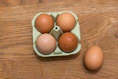 Großaufnahme von rohen Hühnereien im Eikasten auf hölzerner Rückseite der Eiche Lizenzfreie Stockfotos