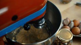 Großaufnahme von weiblichen Händen schaltet den Mischer ein Junge Frau, die den Teig im bown auf der Küche kocht stock footage