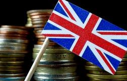 Großbritannien fahnenschwenkend mit Stapel Geldmünzen Lizenzfreie Stockfotos