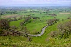 Großbritannien, Gloucestershire, Höchststandpunkt Coaley, kurvenreiche Straße Lizenzfreie Stockfotos
