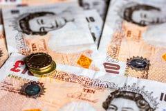 Großbritannien zehn Pfundbanknoten und -münzen Stockbilder