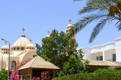Große ägyptische orthodoxe weiße Kirche mit Kreuzen, Bögen, Hauben und Gebetsfenstern gegen den Hintergrund von grünen Bäumen und lizenzfreie stockbilder