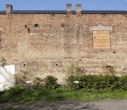 Große alte Backsteinmauer mit blindem Fenster und zwei Direktoren, die Zeichen parken stockfoto