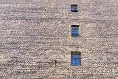 Große alte Backsteinmauer mit Fenstern Lizenzfreie Stockbilder