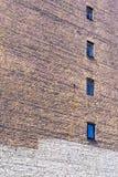 Große alte Backsteinmauer mit Fenstern Lizenzfreie Stockfotos