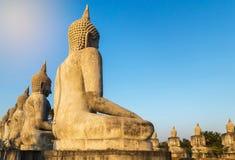 Große alte Buddha-Statuen der hinteren Ansicht, die in der Reihe auf allgemeinem thailändischem Tempel sitzen Lizenzfreies Stockbild