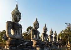 große alte Buddha-Statuen, die in der Reihe auf allgemeinem thailändischem Tempel sitzen Lizenzfreies Stockfoto
