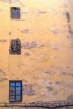 Große alte vergipste Backsteinmauer mit Fenstern Stockfoto