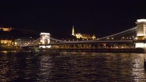 Große Ansicht der Hängebrücke nachts mit dem Boot, das durch den Fluss überschreitet stock footage