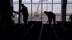 Große Baustelle Eine Gruppe Arbeitskräfte nimmt an auslaufendem Eisen zu einer Betonplatte teil stock footage