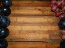 Große blaue Pflaumen und Trauben auf den Seiten der hölzernen Küche verschalen Lizenzfreie Stockbilder