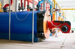 Große blaue Warmwasserboiler mit einem rot-farbigen Gasbrenner stockbild