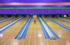 Große Bowlingbahn mit einem Ball, der unten den Weg rollt Stockfotografie