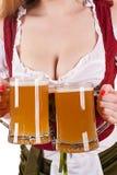 Große Brüste Oktoberfest-Kellnerin mit zwei Bechern Stockbild