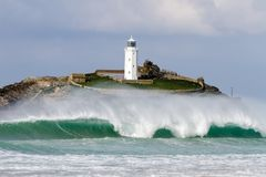 Große brechende Welle vor Leuchtturm Stockfotografie