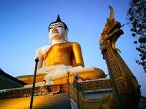 Große Buddha-Statue in der Goldfarbe auf der Rückseite ist- Abend des blauen Himmels Lizenzfreie Stockfotos