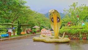 Große bunte Kobraschlangenstatue auf Straße durch Blumenbeet stock video