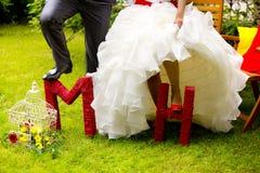 Große dekorative rote Buchstaben - M und H - und Beine des Mannes addieren Frau - Braut und Bräutigam Stockfoto