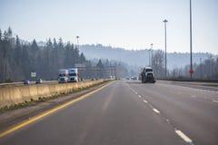 Große der Anlagen LKWs halb und ein anderer Autoverkehr in beiden Richtungen auf geteilte Landstraße stockfoto