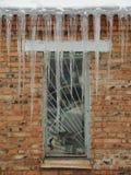 Große Eiszapfen über dem Fenster Stockbilder