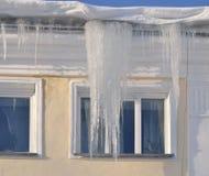 Große Eiszapfen auf einem Hausdach Lizenzfreie Stockfotografie