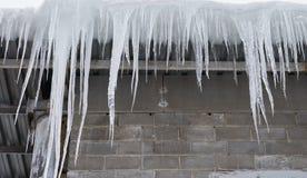 Große Eiszapfen, die auf einem Dach überhängen lizenzfreies stockfoto