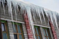 Große Eiszapfen, die am Dach hängen lizenzfreie stockfotografie