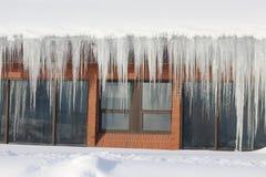 Große Eiszapfen, die von einem Kirchendach hängen Lizenzfreie Stockbilder