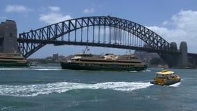 Große Fähren und ein kleines Wasser fährt das Überschreiten durch Hafenbrücke in Sydney mit einem Taxi stock footage