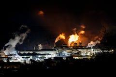Große Fabrik nachts mit Feuer und Licht stockfoto