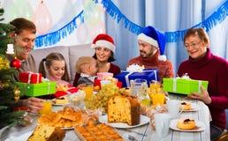 Große Familie, die Geschenke während des Weihnachtsessens austauscht Stockbilder