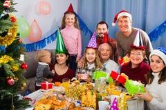 Große Familie, die Geschenke während des Weihnachtsessens austauscht Stockfoto