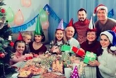 Große Familie, die Geschenke während des Weihnachtsessens austauscht Stockfotos
