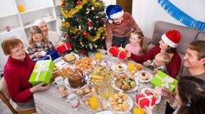 Große Familie, die miteinander Geschenke übergibt Stockfotos