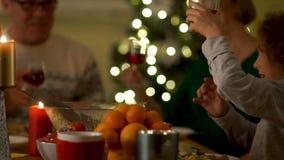 Große Familie feiert neues Jahr Großvater und Großmutter sitzen am Tisch mit ihrem Enkel Geklirrgläser stock video