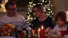 Große Familie mit den Kindern, die zu Hause Weihnachten feiern Festliches Abendessen am Kamin und an Weihnachtsbaum Elternteil un stock footage