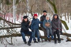 Große Familie sitzen auf Baumstamm im Winterwald Lizenzfreie Stockbilder
