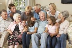 Große Familien-Gruppe, die auf Sofa Indoors sitzt Stockbild