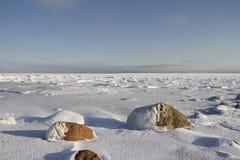 Große Felsen unter Schnee und Eis mit einem blauen Himmel in der Arktis Lizenzfreie Stockfotos