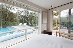 Große Fenster, die Ansicht zeigen, um im Luxushaus zu vereinigen und im Garten zu arbeiten Lizenzfreies Stockbild