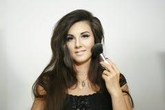 Große flaumige Bürste des sexy schönen Make-upmädchen-Gebrauches, Blicke auf Sie mit hellem Lächeln Stockbilder