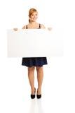 Große Frau, die ein weißes Brett hält Lizenzfreie Stockbilder