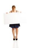 Große Frau, die ein weißes Brett hält Stockfotos