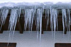 Große gefährliche Eiszapfen auf einem Hausdach im Winter lizenzfreies stockfoto