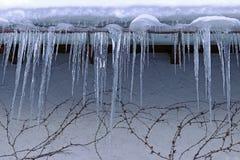 Große gefährliche Eiszapfen auf einem Hausdach im Winter stockfotografie