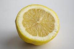Große gelbe Zitrone liegt auf einer blauen Platte auf einem gelben Hintergrund Stockfotografie