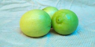 Große gelbe Zitrone liegt auf einer blauen Platte auf einem gelben Hintergrund stockbild
