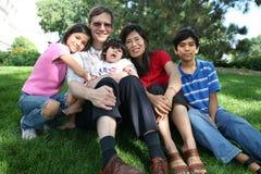 Große gemischtrassige Familie, die auf Rasen sitzt Stockfotos