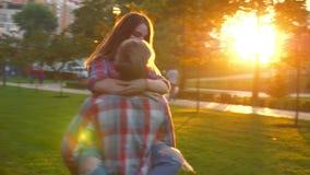 Große Gesamtlänge der Liebe, Junge küsst seine Freundin und hält sie mit den Händen, schaltet Kreis ein und bewegt sich in Grün stock video footage