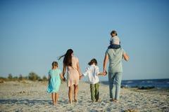 Große glückliche Familie, die am Strand geht Mutter, Vati und drei Kinder Der blaue Himmel, die Sonne, frischer Seewind Vergnügen Lizenzfreies Stockbild